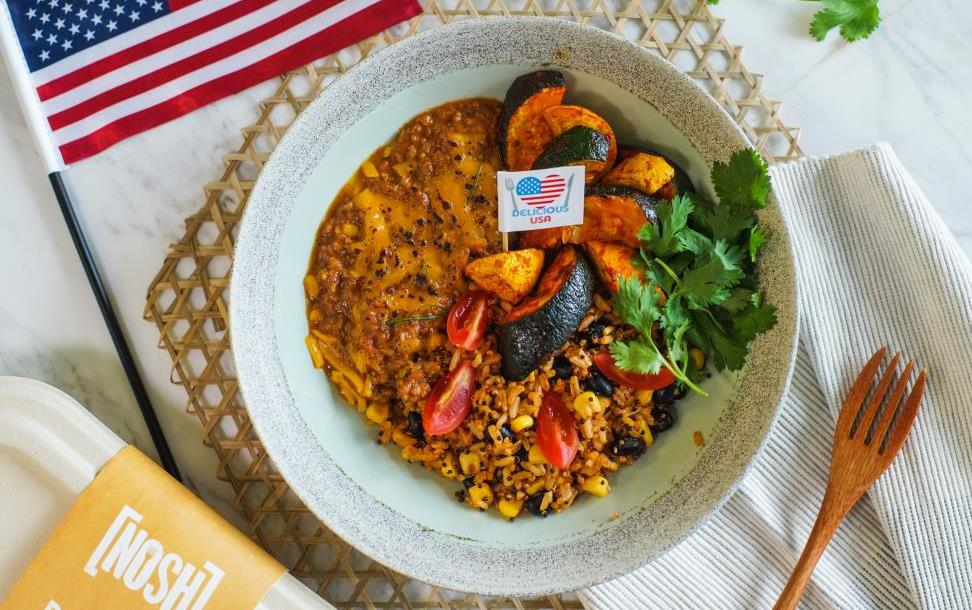 Bowl of chili on bamboo placemat flanked by American flag and wooden fork