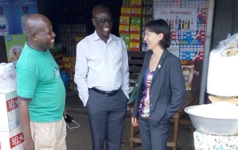 White woman wearing business suit stands with two casually dressed black men in street market stall