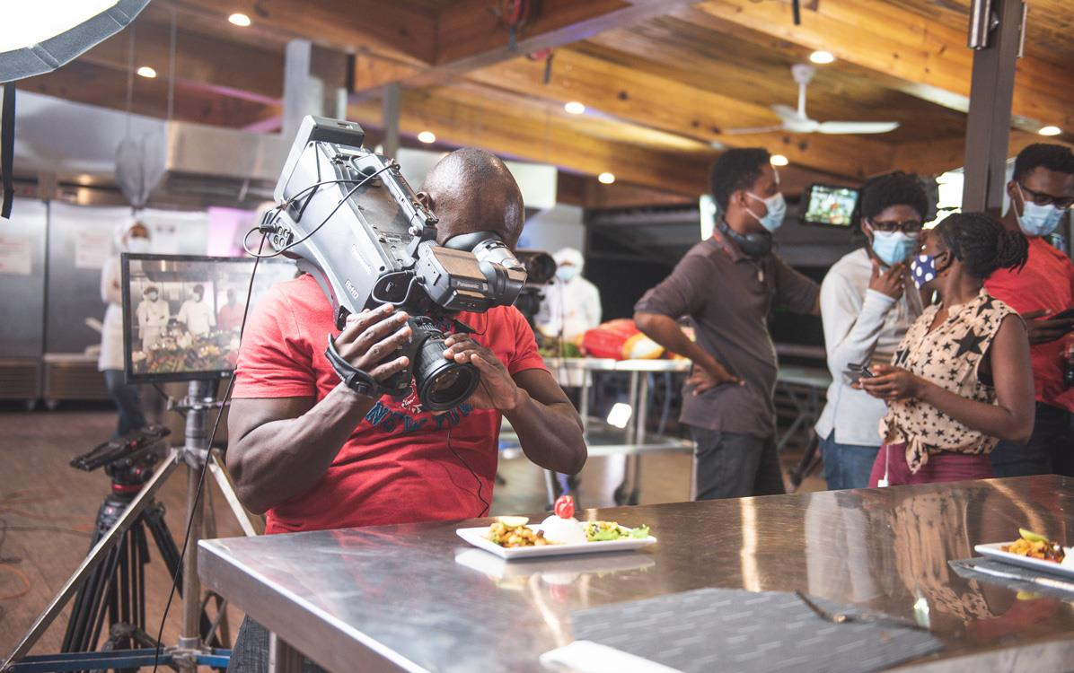 Man filming close-up of rice dish on stainless steel table, people wearing face masks in background