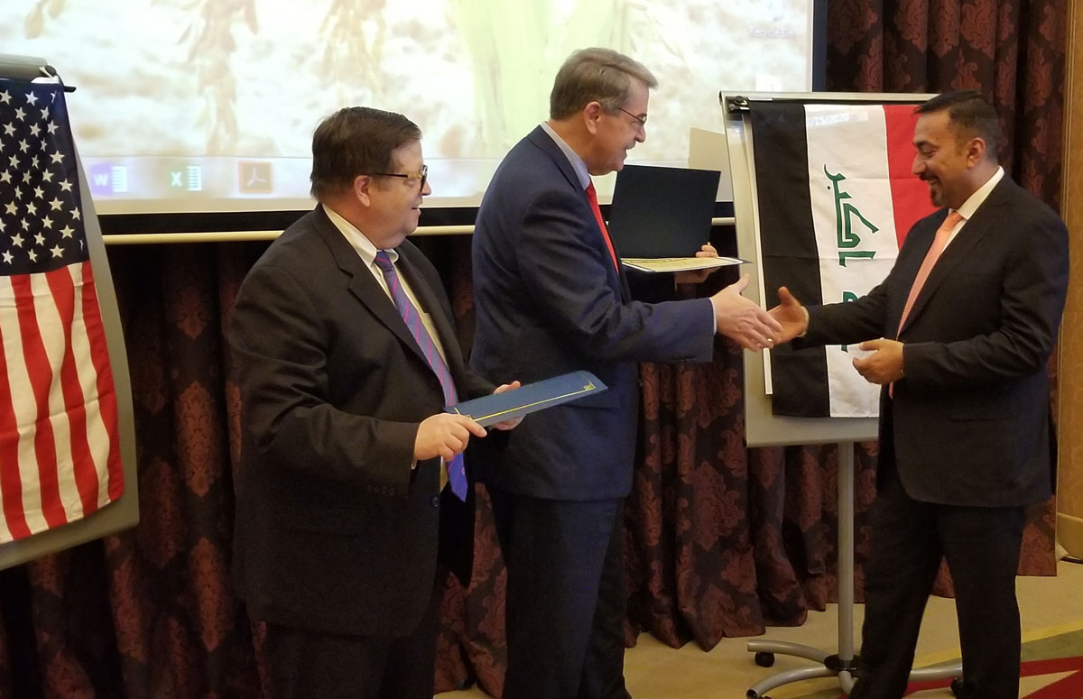 Two men in business suits shake hands while another businessman looks on, US and Iraq flags flank them