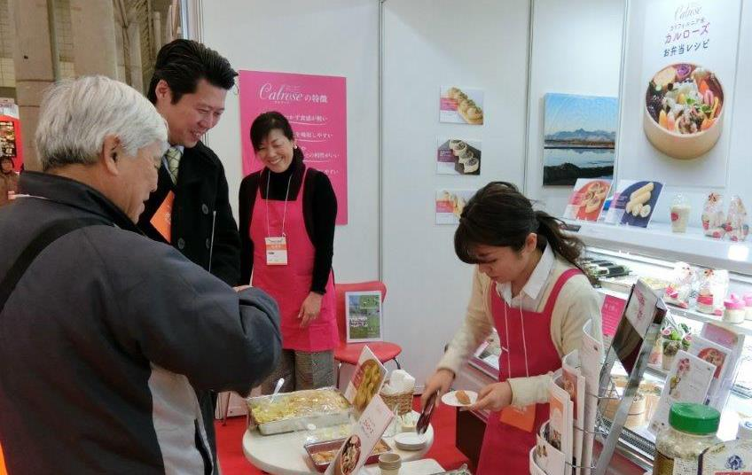 Japanese Supermarket Trade Show, women wearing pink aprons serve rice samples to two men standing in front of display case