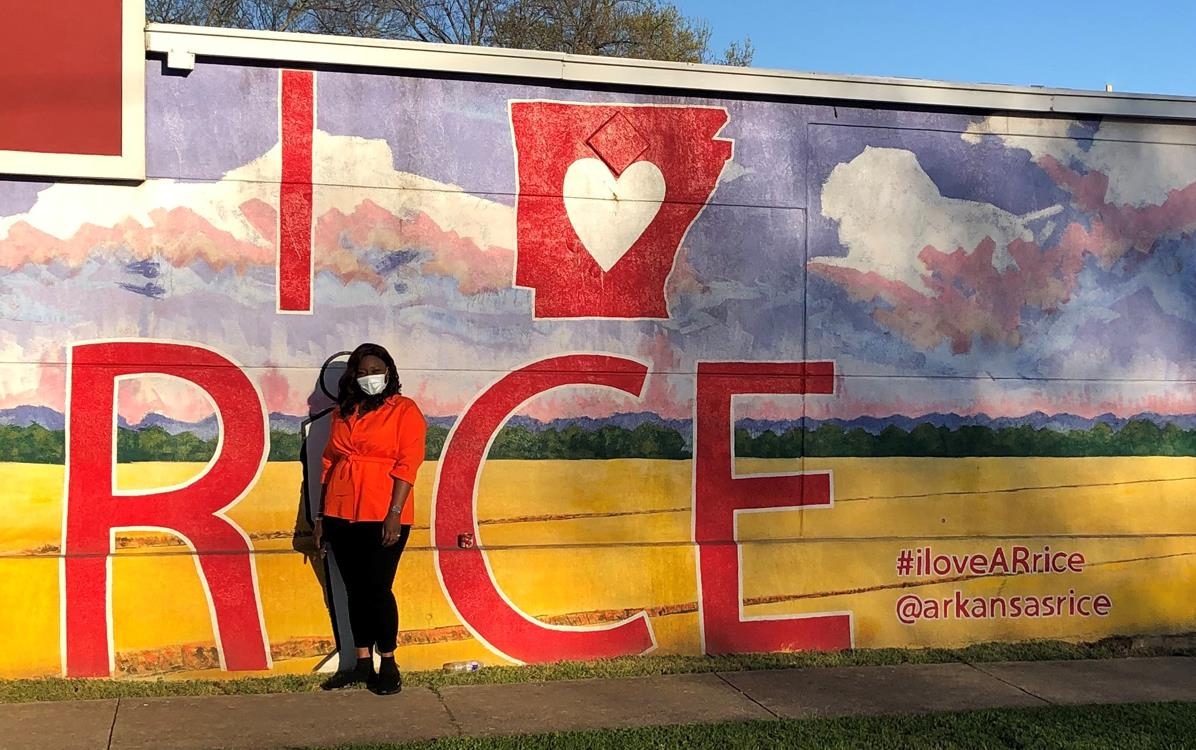 Black woman stands in front of I HEART Arkansas rice-mural