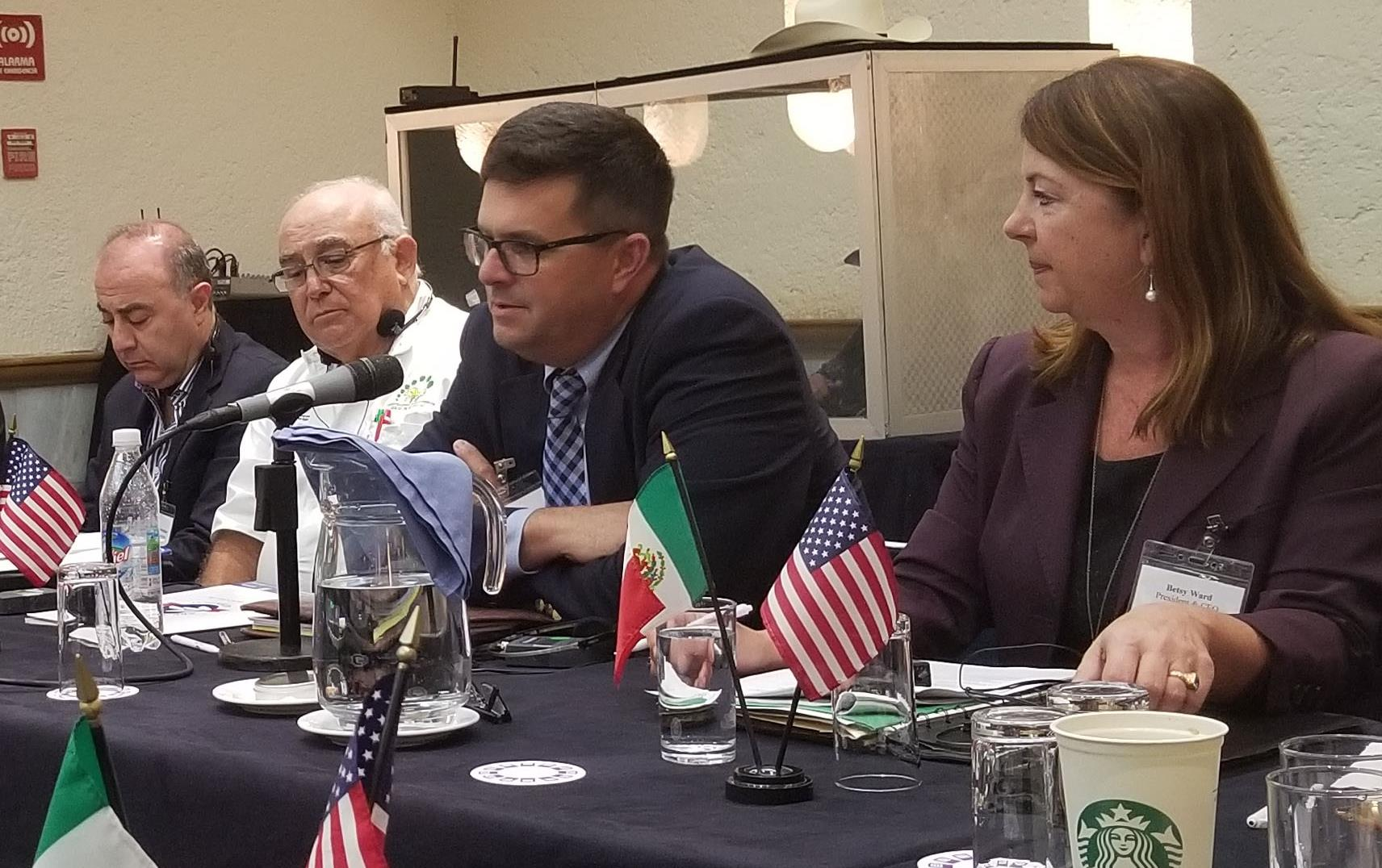 Trade Mission to Mexico, people sitting around board room table with small US & Mexican flags