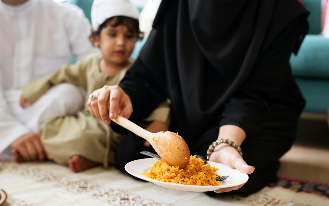 Woman serves Ramadan rice meal, child and man in background