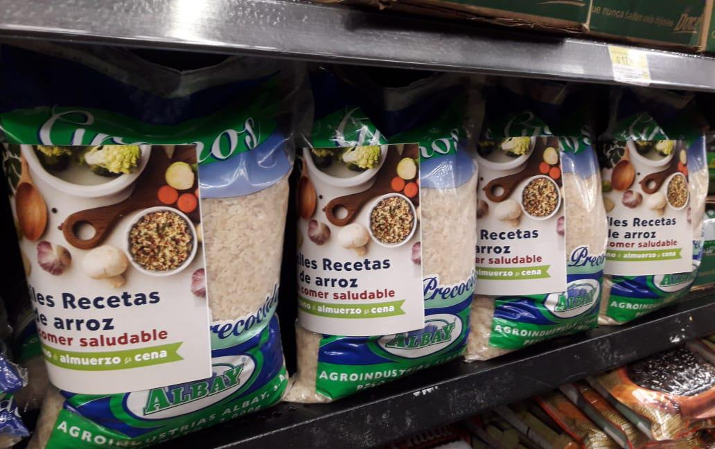 Recipe books on bags of rice stacked on grocery store shelves