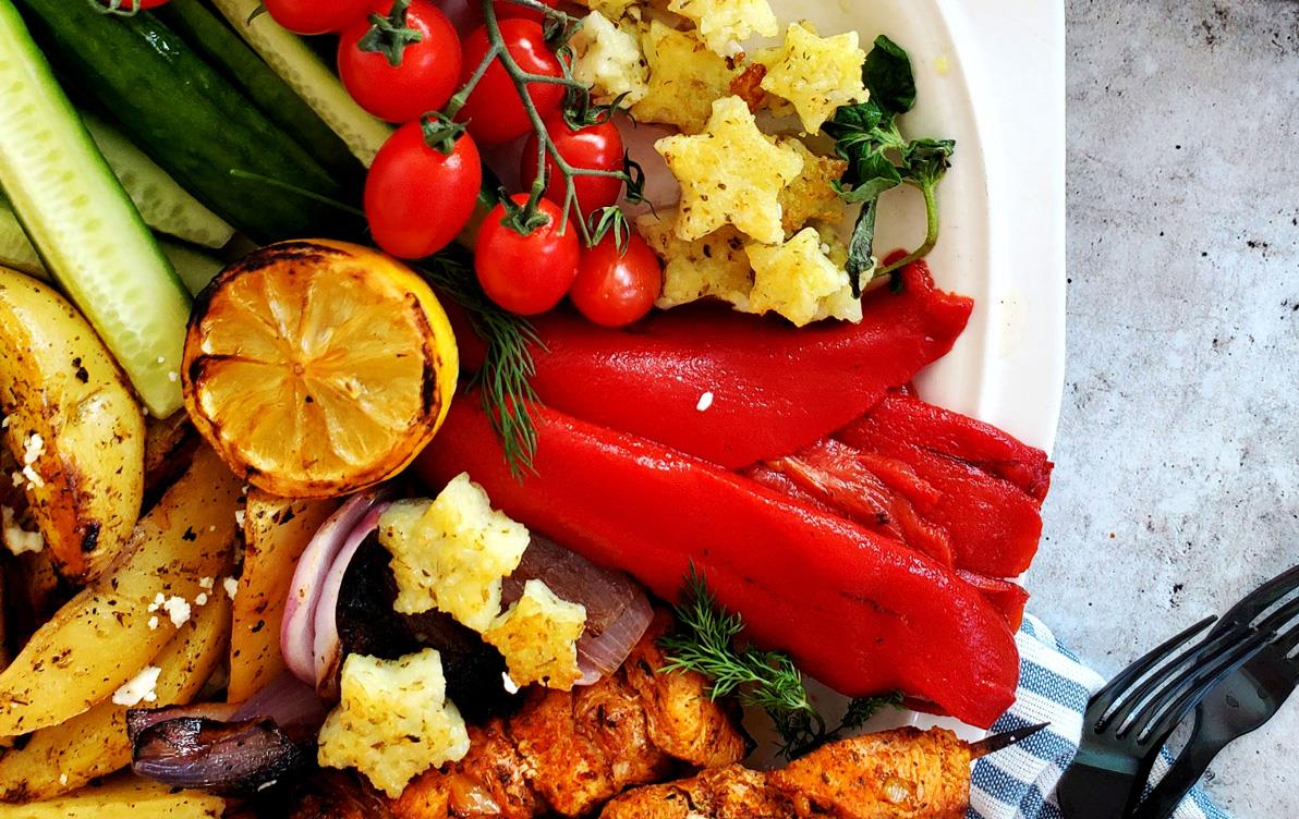 Star-shaped rice croutons in white bowl with red tomatoes and peppers, squash, chicken, lemons with a bowl of raw rice on the side