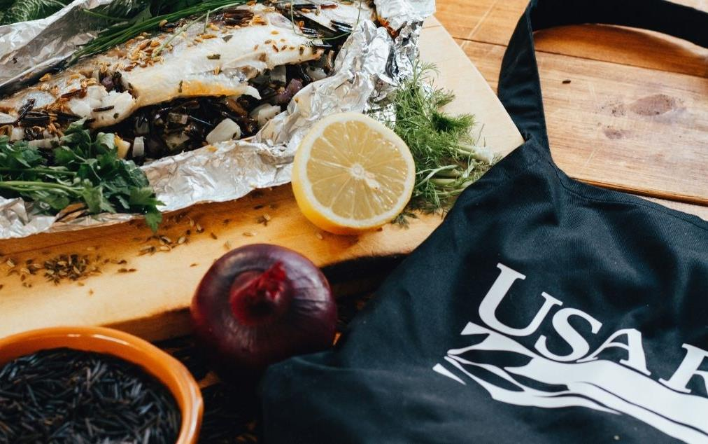 Sea-Bass stuffed with wild rice, wrapped in foil, on cutting board, next to USA-Rice-Apron
