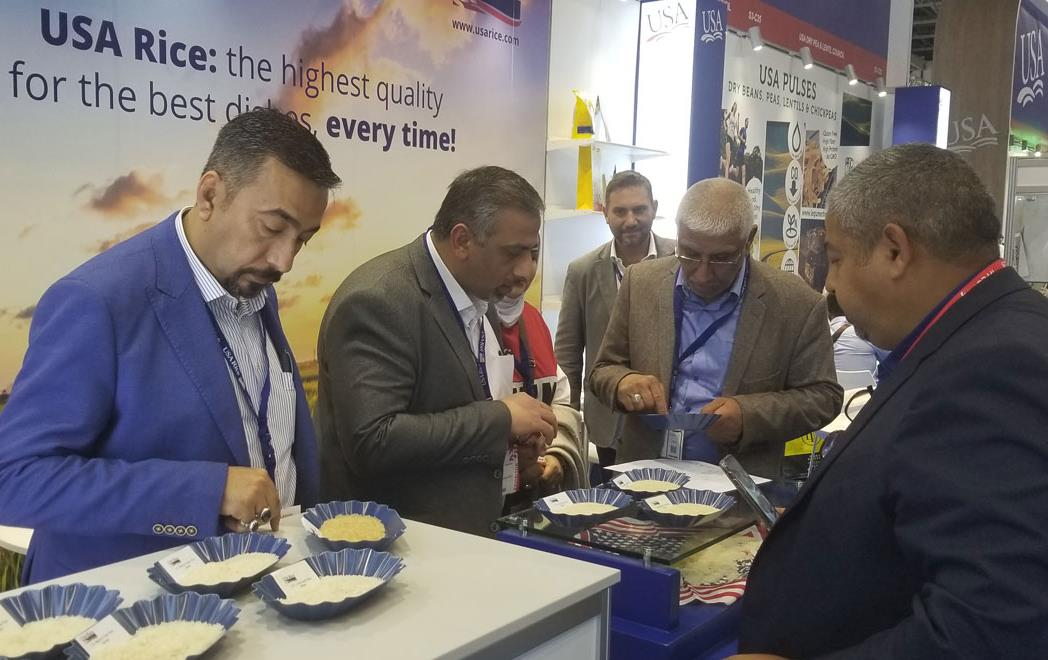 USA-Rice-Booth-at-Gulfood-Show, group of men stand at table examining rice samples in small blue bowls