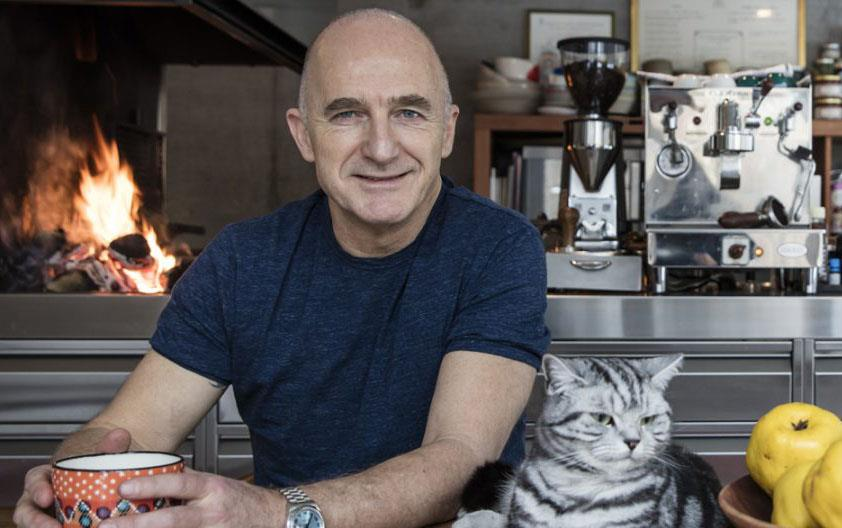 Bald white man wearing dark shirt, holds a cup in his hands, gray tabby cat and bowl of golden pears next to him, fire and kitchen equipment in background