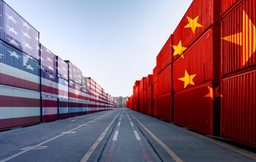 Shipping containers on a loading dock, stack on left side painted with US flag, stack on right side painted with Chinese flag