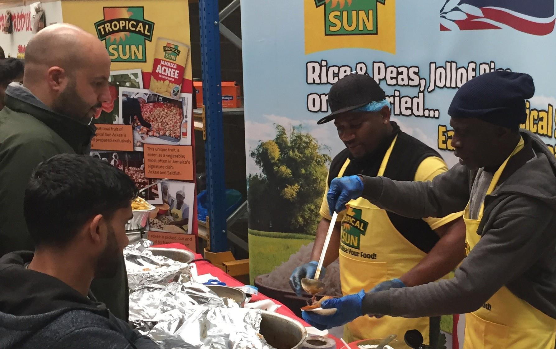 People gather at a buffet table filled with colorful dishes being served by two black men wearing yellow aprons standing in front of a USA Rice & Tropical Sun banner