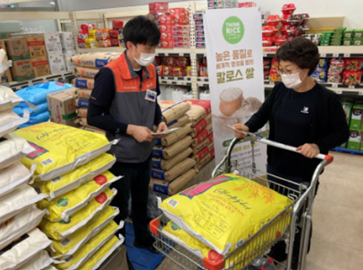 Korea promotion shows two people, both wearing masks, the man is holding papers and the woman is pushing a grocery cart filled with yellow bags of rice