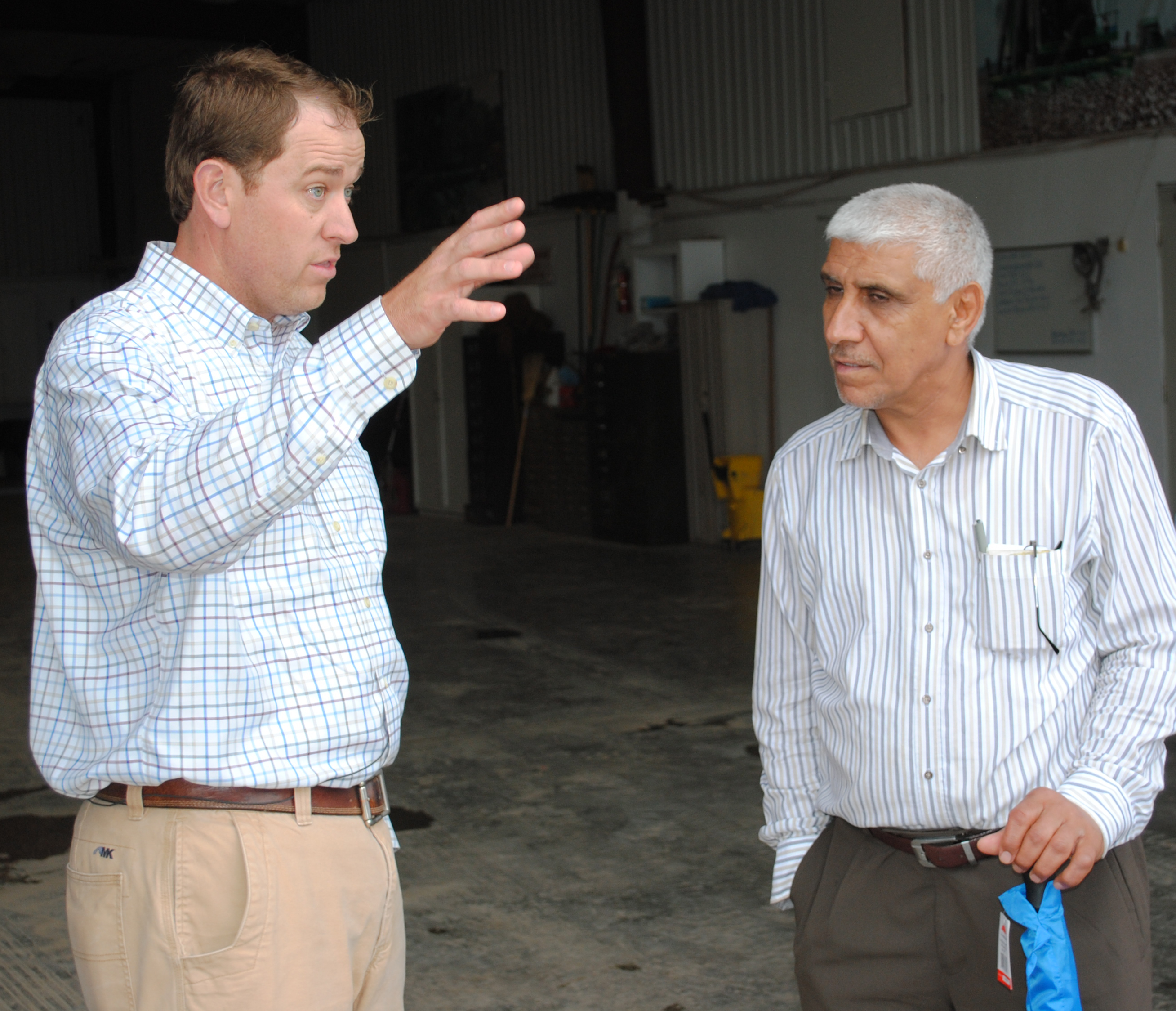 Two men wearing long-sleeved button-down shirts meet inside an equipment shed, one on the left gesturing with one hand, one on the right listens intently