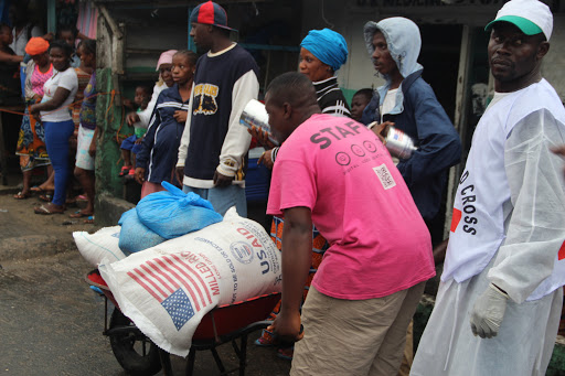 Man wearing pink t-shirt pushes wheelbarrow filled with bags of USAID milled rice in front of line of people