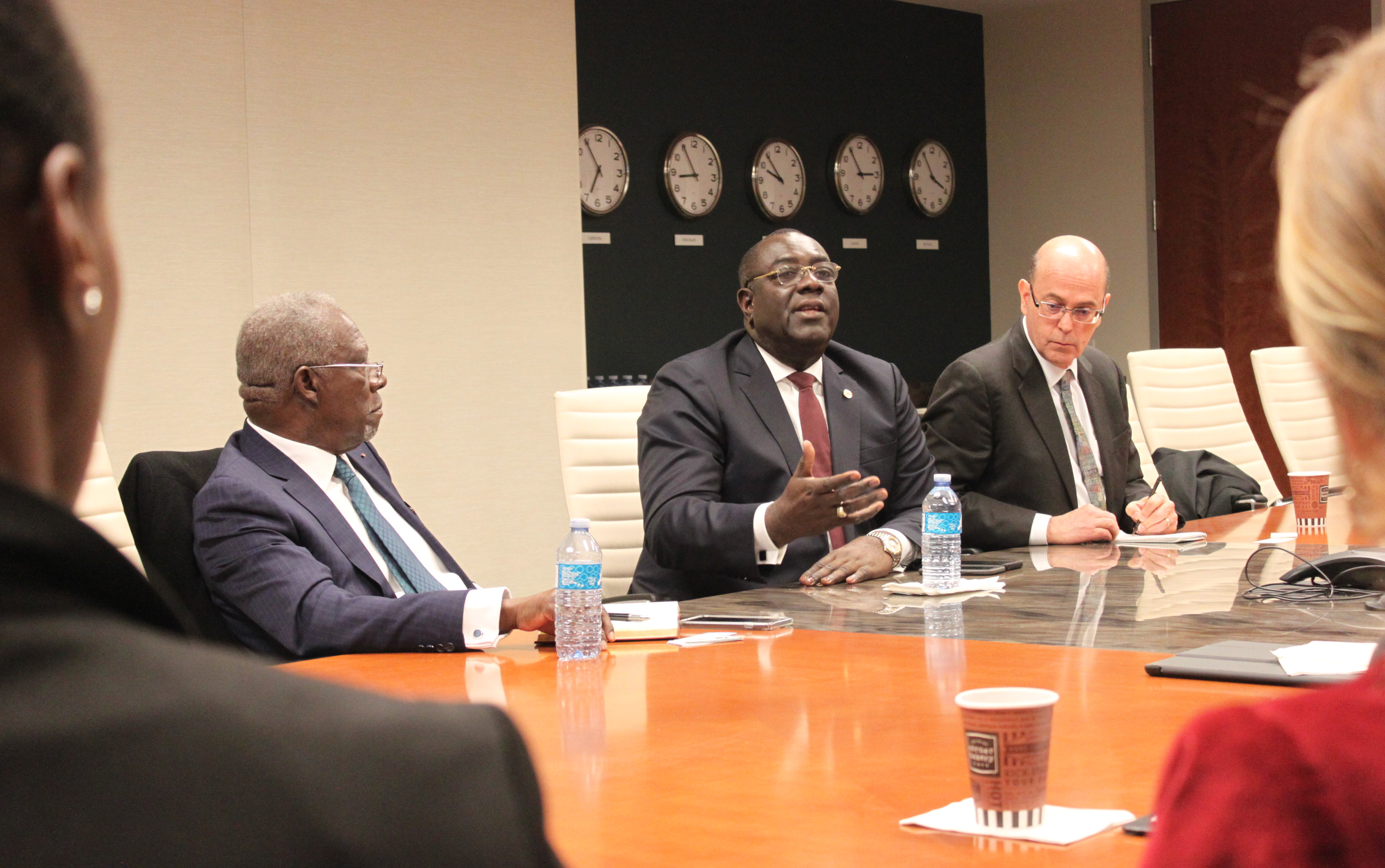 Haiti Foreign Minister Bocchit Edmond (black man wearing business suit) sits at conference table with two other men wearing business suits, wall full of clocks in background