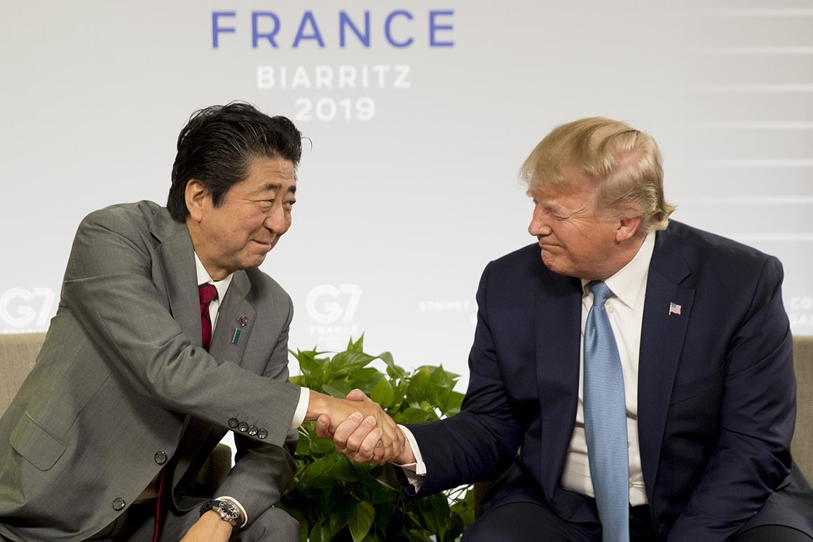 Japanese Prime Minister Shinzo Abe shakes hands with US President Donald Trump, both men wearing business suits, seated in front of backdrop reading Biarritz 2019