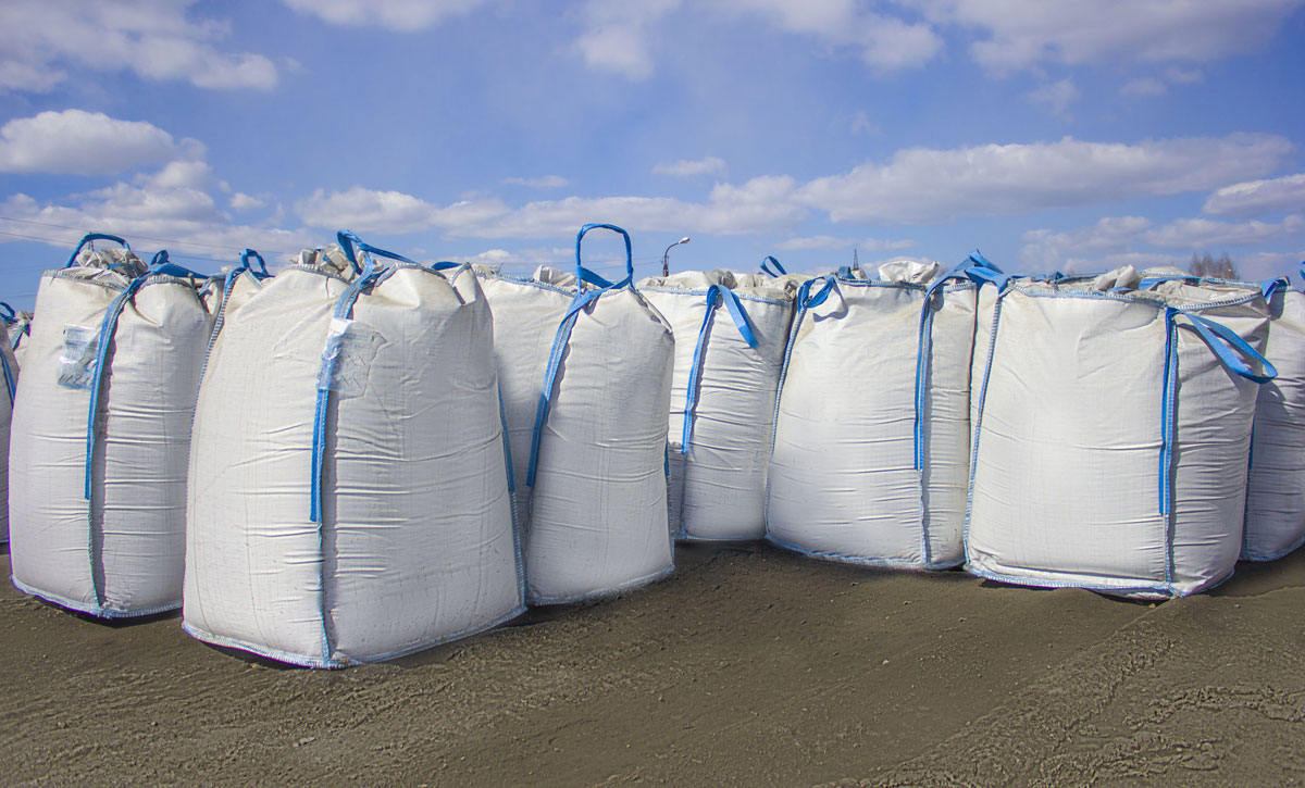 Large-white rice-sacks-lined-up, blue sky in background