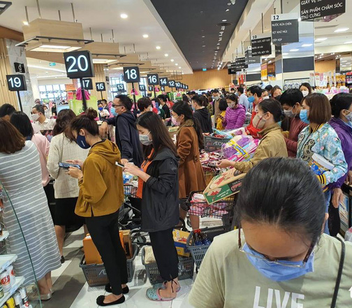 Crowds at grocery store wearing masks, standing in checkout lines, panic buying