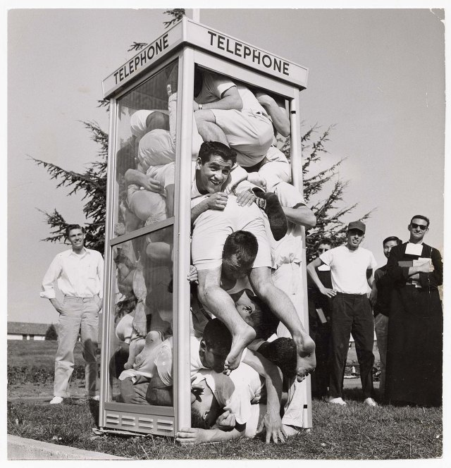 Black & white photo of men crammed into an old fashioned phone booth, bystanders in the background
