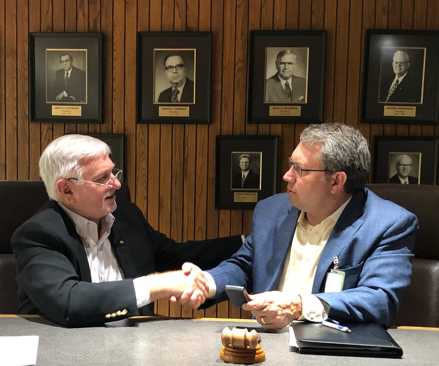 Two men wearing sport coats sit at table with gavel shaking hands, portrait photo gallery in background