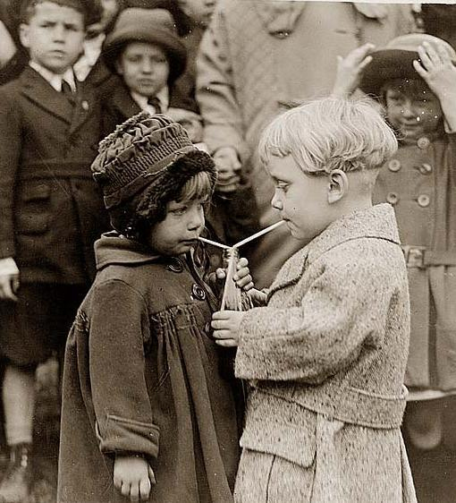 B/W photo of two children drinking out of same soda bottle with two straws