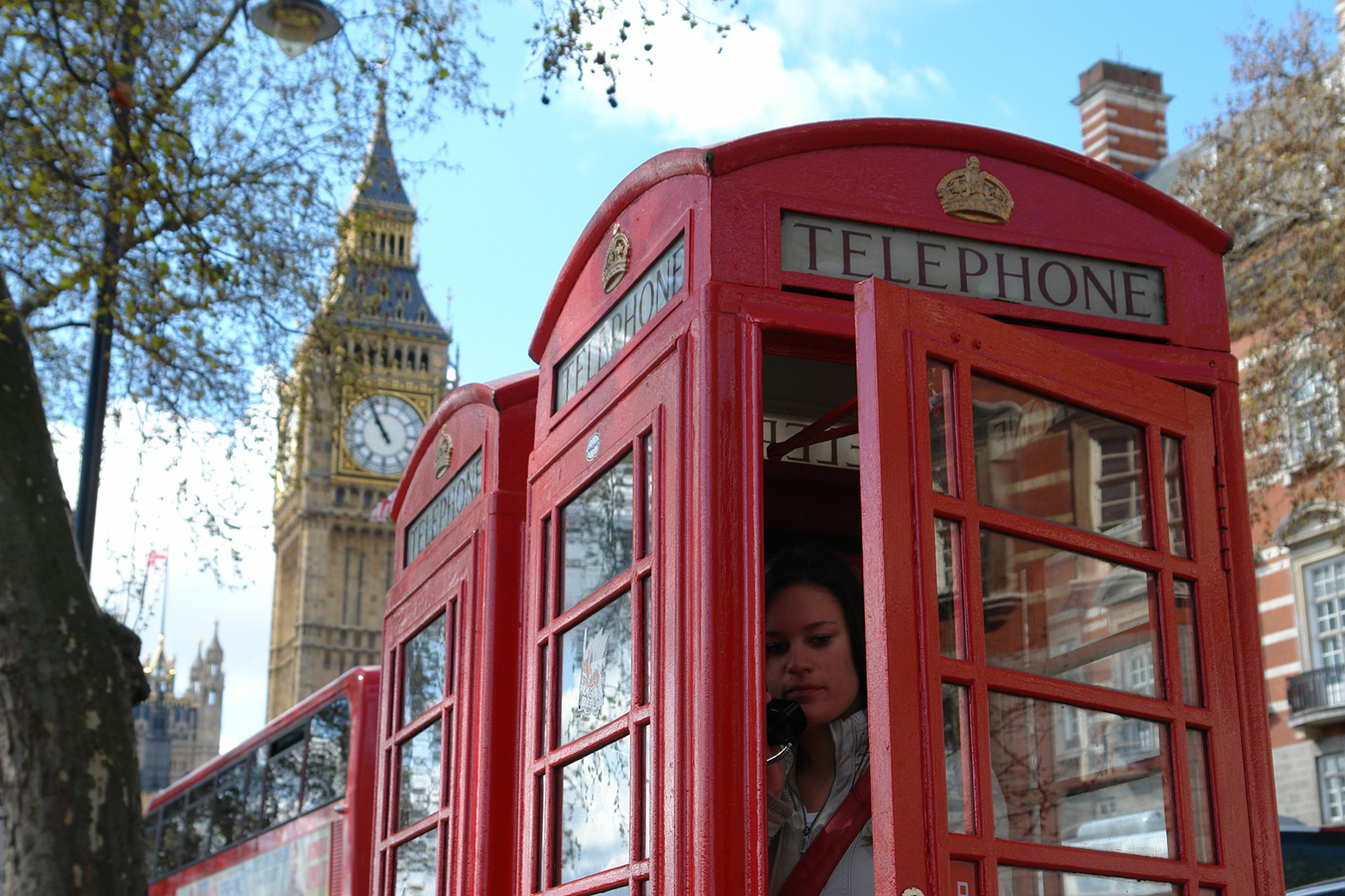 Woman on the phone inside a red UK telephone box, Big Ben in background