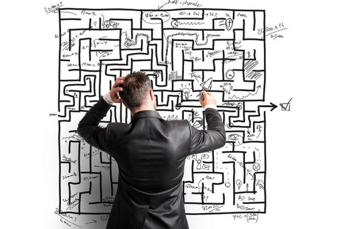 Man in dark suit standing in front of a maze drawn on a white board, scratches his head trying to find a way out