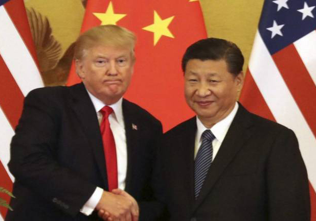 Donald-Trump-with grim face shakes hands with China's premier Xi-Jinping, standing in front of Chinese and US flags
