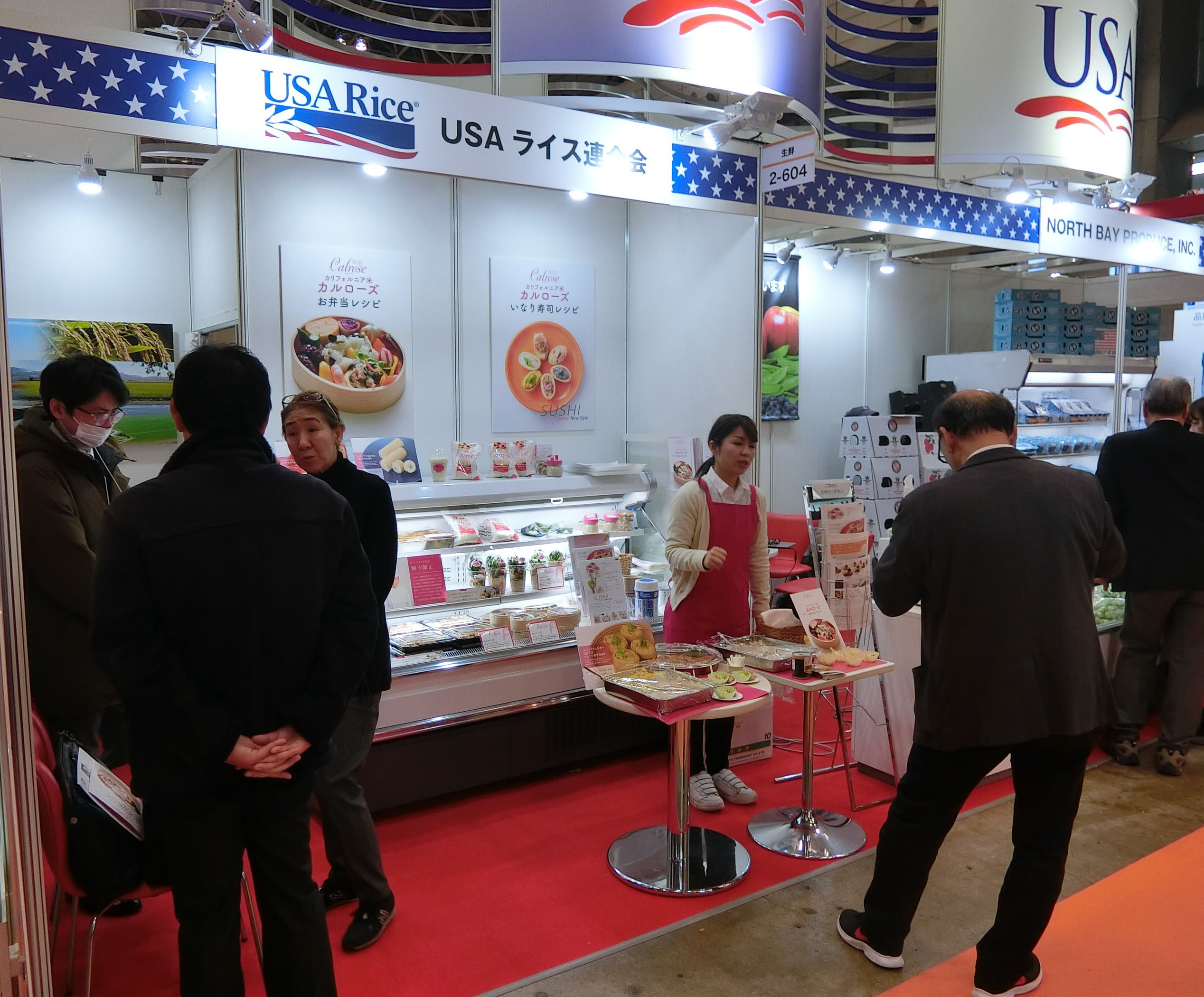 Trade show booth with people standing around talking, a woman wearing a red apron offers food samples to man wearing black suit