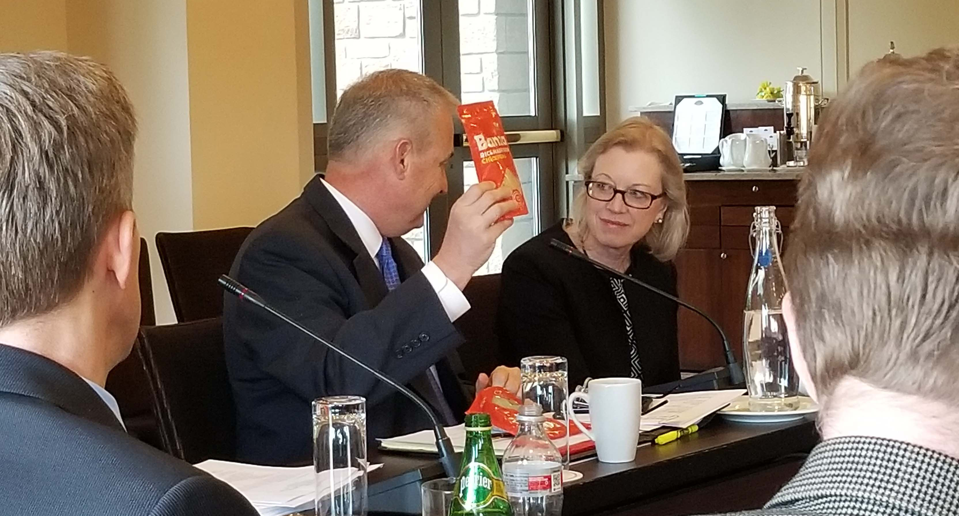 At a business meeting a man holds up a small, orange package while a woman wearing glasses smiles at him