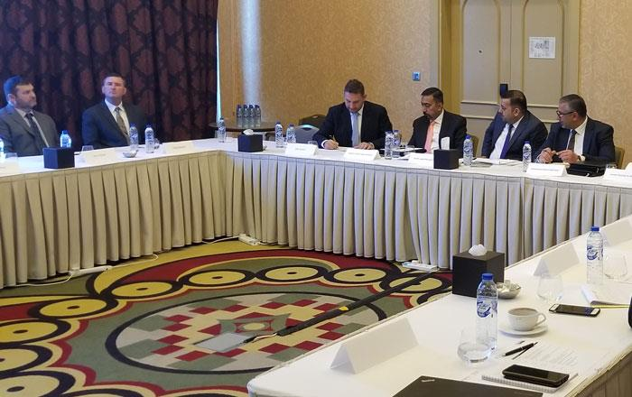 Group of people wearing business attire sit around large conference room table