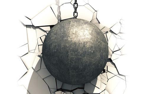 Iron wrecking ball smashes into white wall