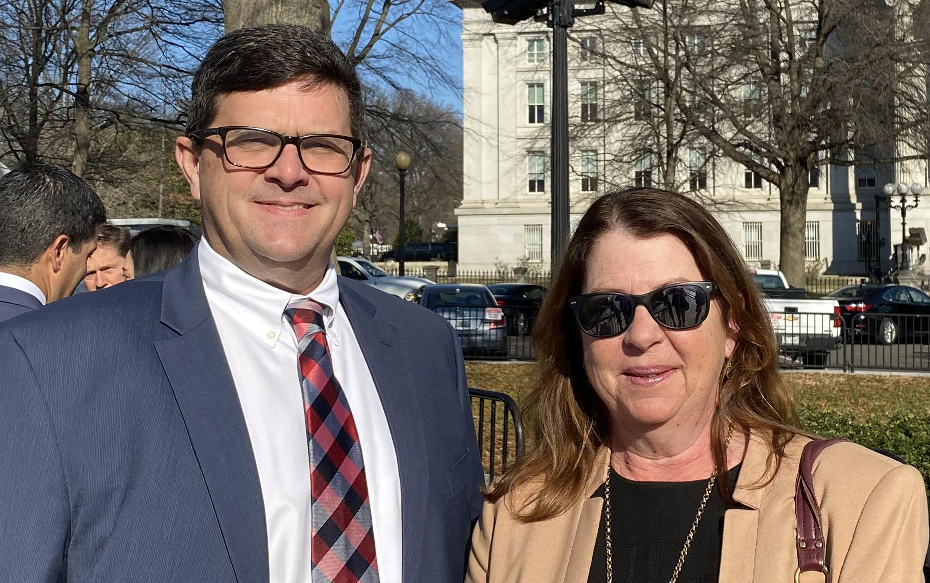 Man and woman dressed in business clothes stand outside in White House security line
