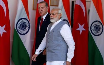 Two older men walk in front of flags of Turkey and India, one wears a business suit, the other wears a white shirt and light blue vest