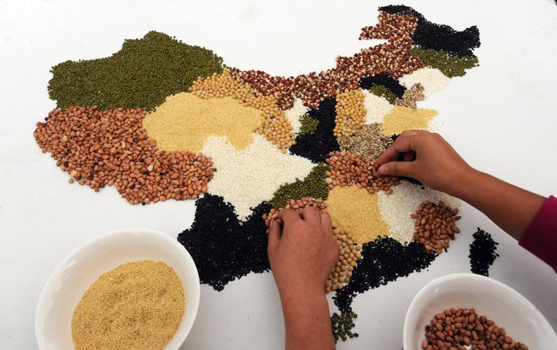 Two hands creating map being made with colorful grains