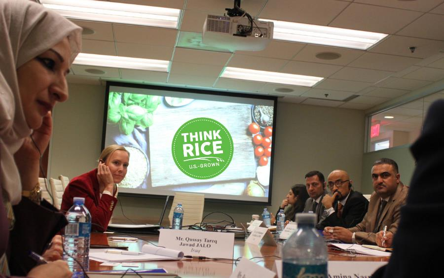 People wearing headphones sit around conference table, green Think Rice logo prominent on video screen in room