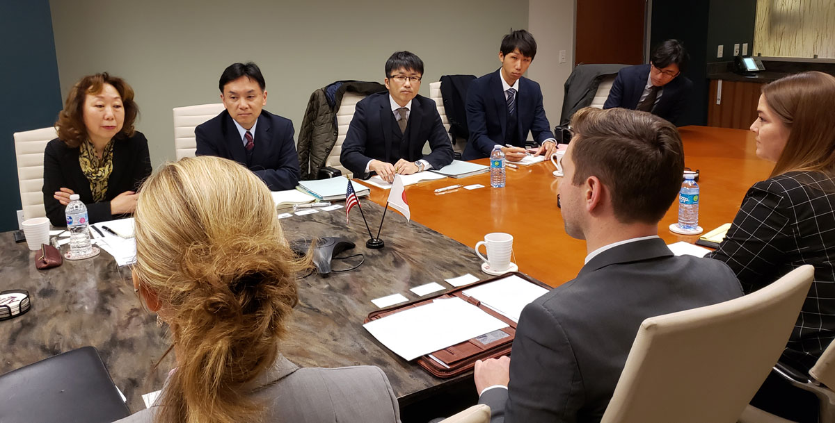 Group shot of people sitting around conference room table