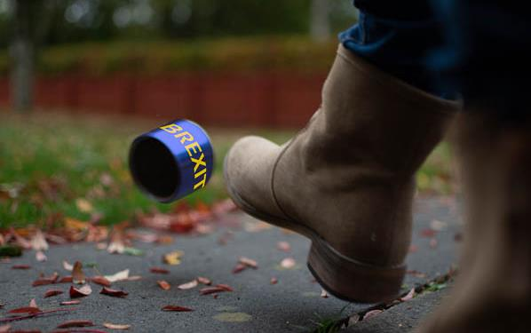 "Boot kicking can that says ""Brexit"" down a leaf-strewn road"