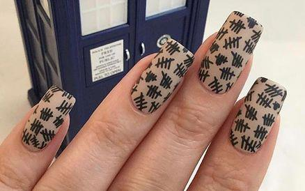 Black tally marks painted on manicured nails