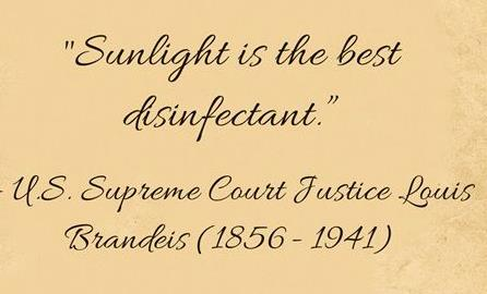 "Text ""Sunlight is the best disinfectant"" on yellowed book page"