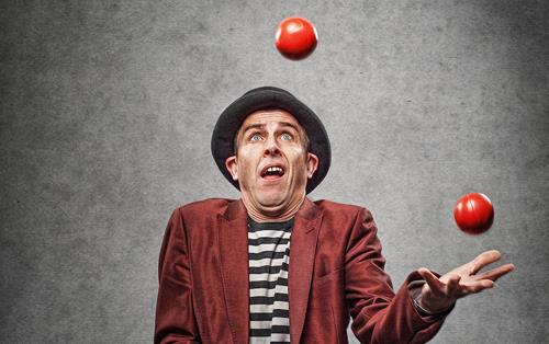 Man wearing burgundy suit and bowler hat juggles three red balls