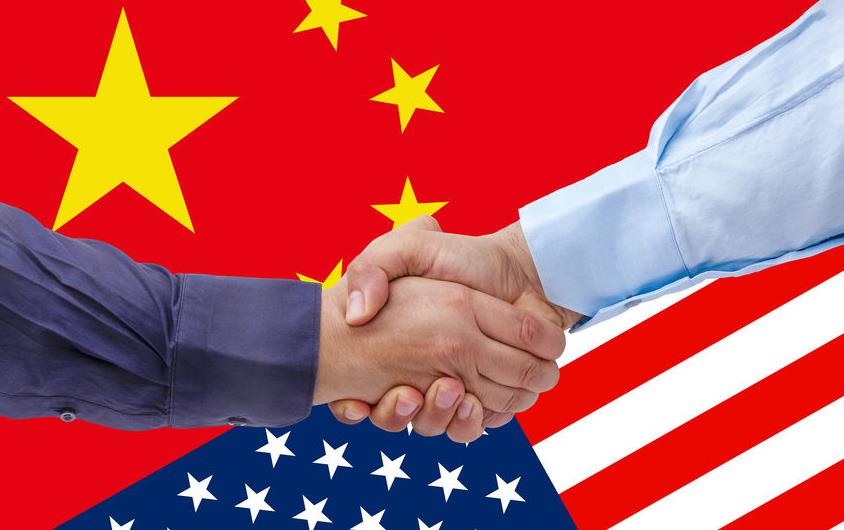Handshake over US & China flags