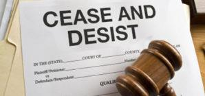 "Wooden gavel covers piece of paper with text ""Cease And Desist"" atop stack of manila files"