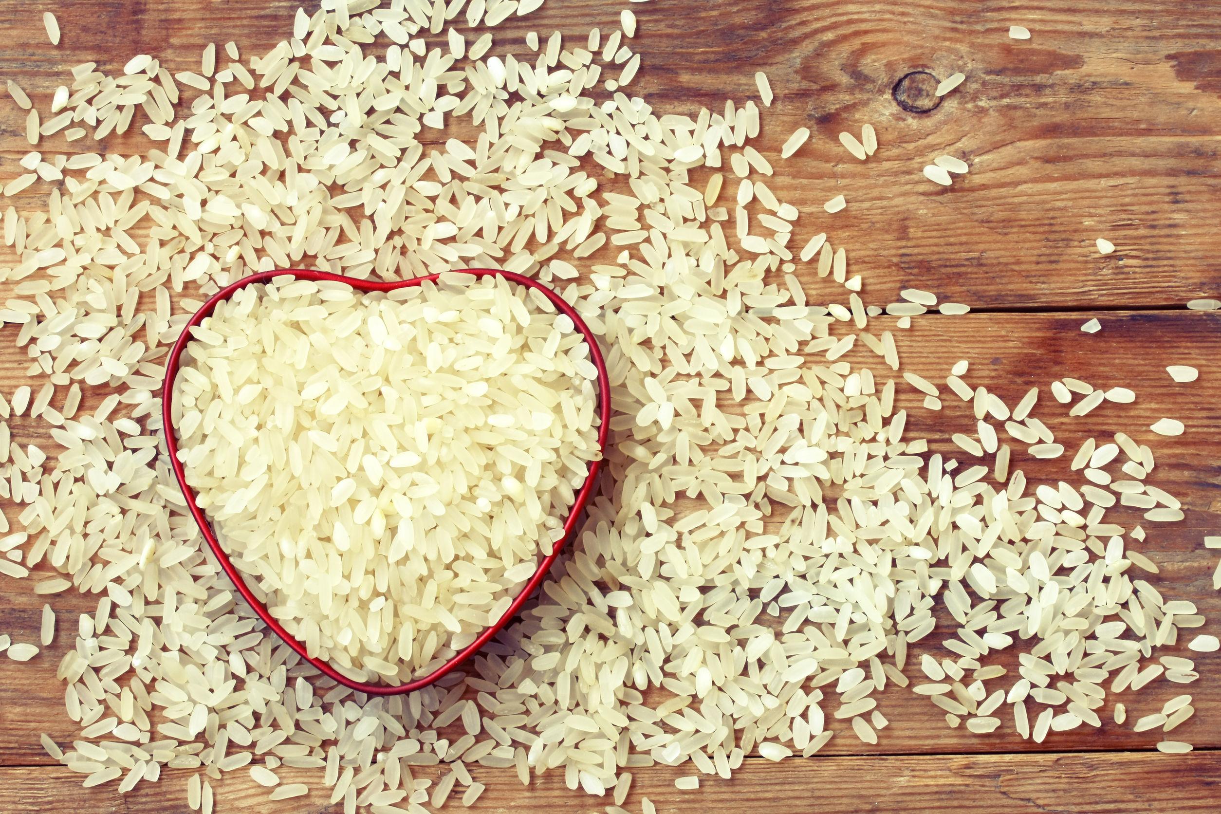 White rice inside red heart shape spilling onto wooden plank