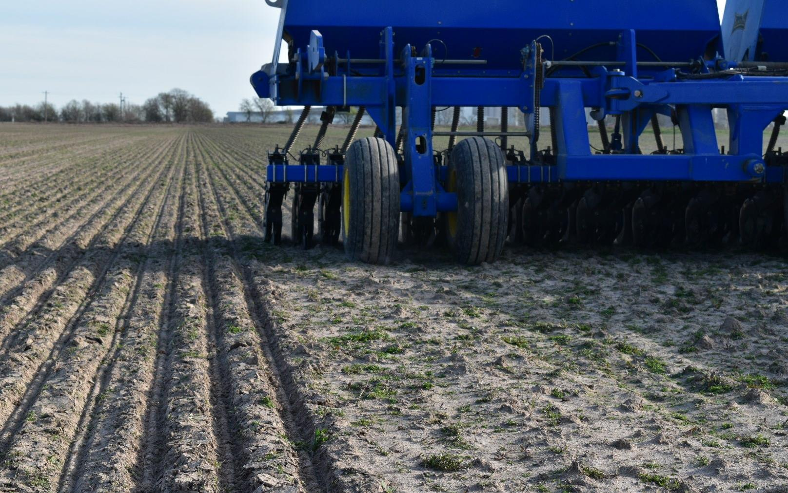 Blue combine creating furrows in new field