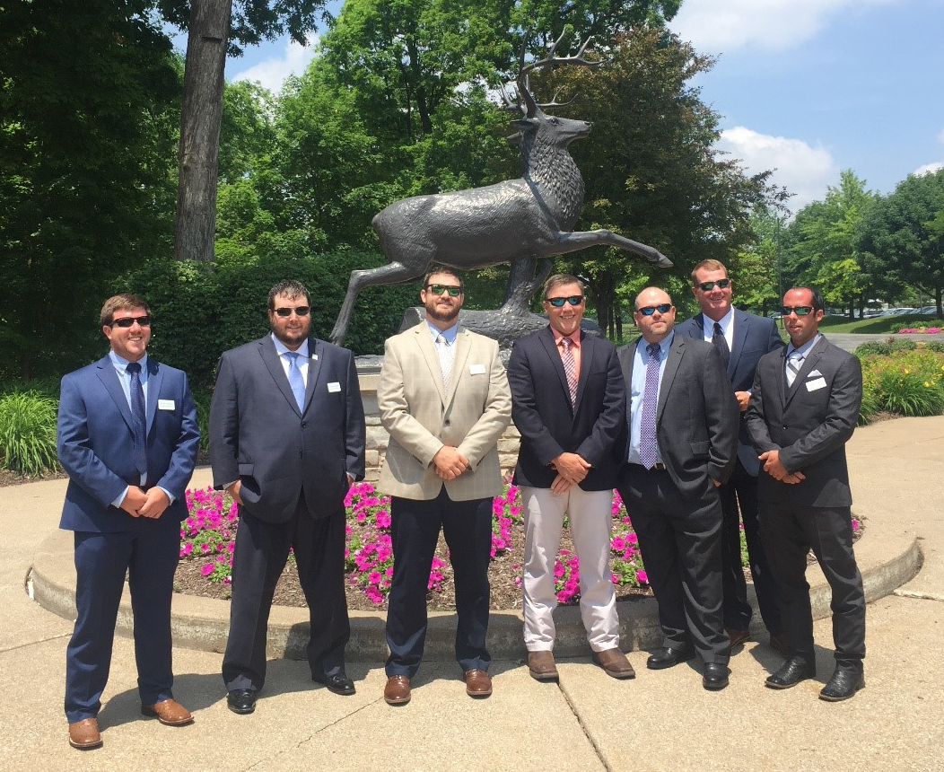 2019-21 Rice Leadership Class, group shot of men wearing suits and sunglasses standing in front of deer statue