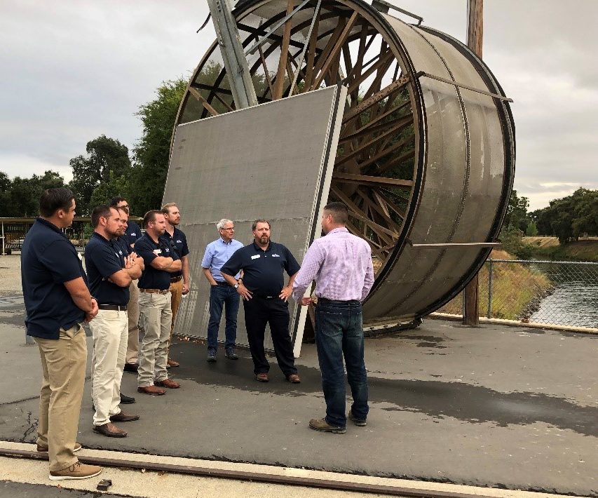 Group of men stand in front of enormous metal water wheel