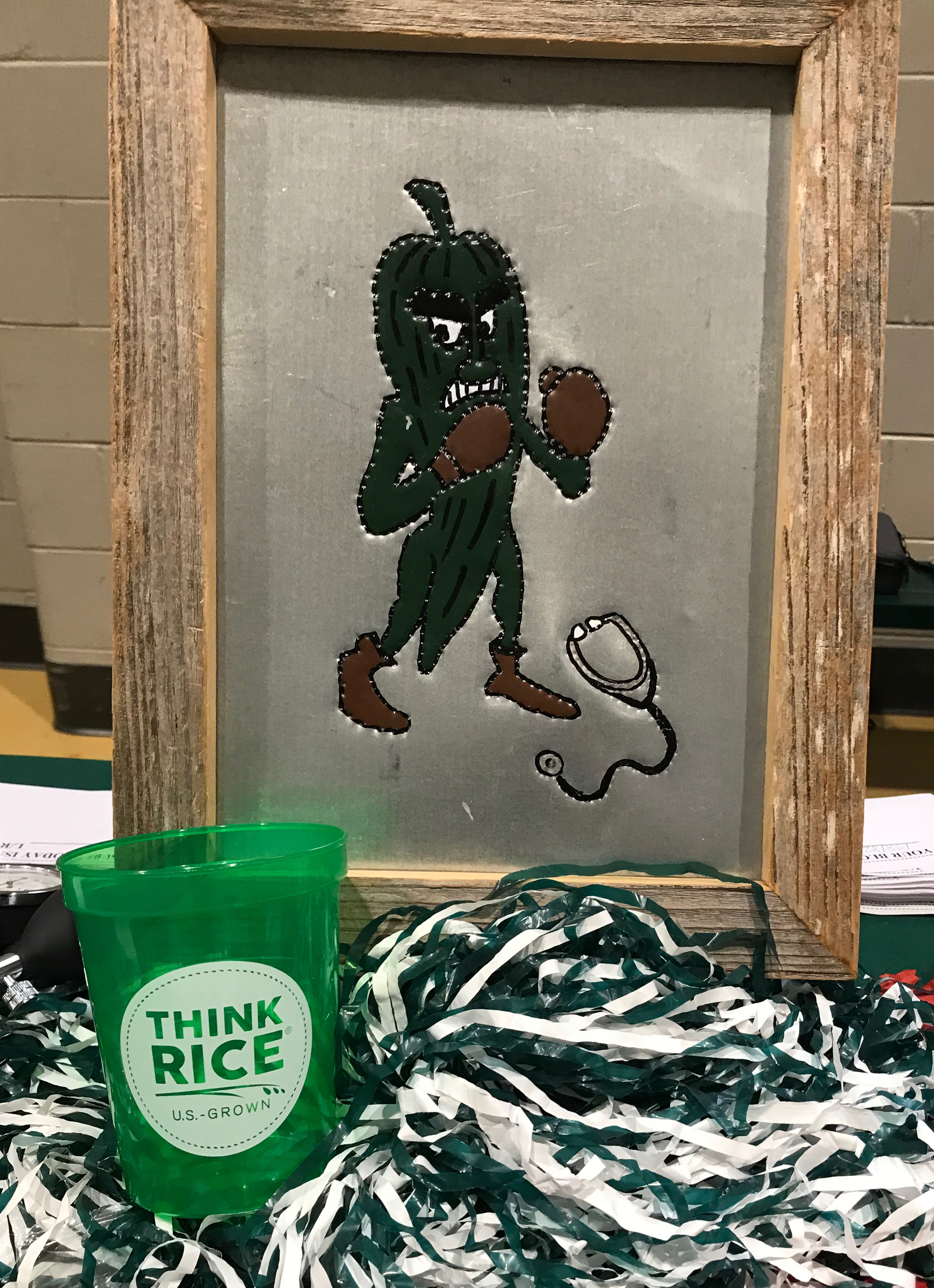 "Framed picture of ""Fighting Okra"" sits on table with Think Rice cup and green & white pom-pom"