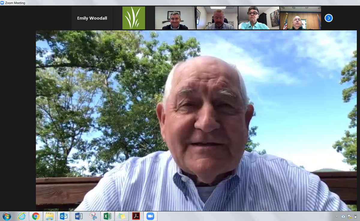 Zoom meeting screenshot shows large picture of older white man with smaller photos of more white people across the top of the screen