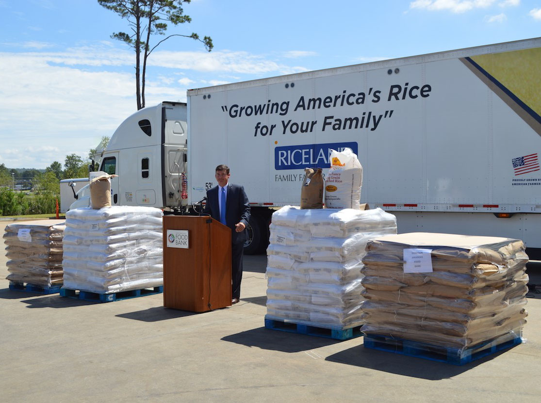 AR Foodbank Donation, Jeff Rutledge stands in front of podium, large bags of rice on pallets and semi-truck in background